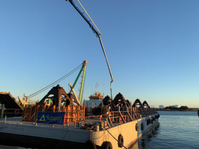 Concrete pour for Wonder Reef anchor pyrimads on a barge on the water against a bright blue sky.