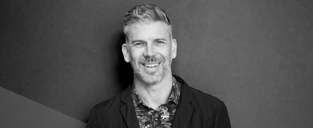 Artist Daniel Templeman smiling in black and white.